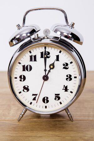 Metallic retro alarm clock on white isolated background.