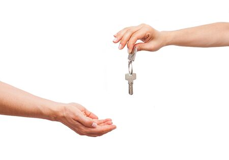 Young female real estate agent is giving the house key. Stockfoto
