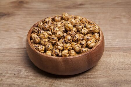 Roasted and dry chickpeas on wooden table.