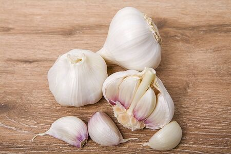 Whole garlic and cloves of garlic on wooden background.