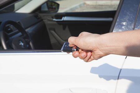 The woman's hand is pushing the button on the ignition key.