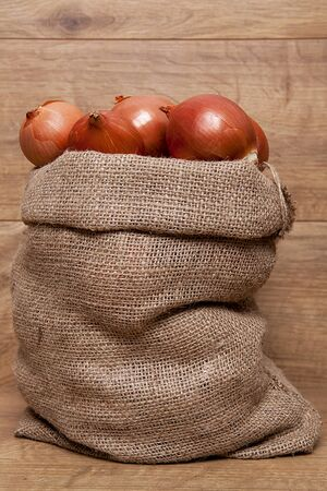 Yellow onion in a sack on wooden background. Banco de Imagens