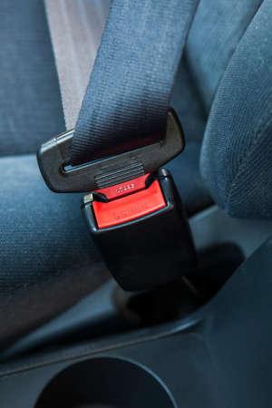 Fastening seat belt in a car.