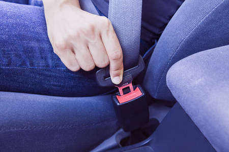 Wearing seat belts in a car. The woman is wearing her seat belt.