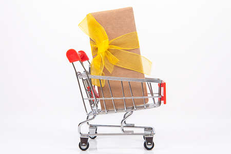 Gift package and small toy shopping cart on table. Internet shopping concept.
