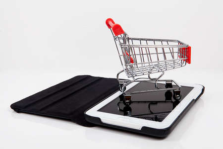 Computer and small toy shopping cart on table. Internet shopping concept. Stok Fotoğraf