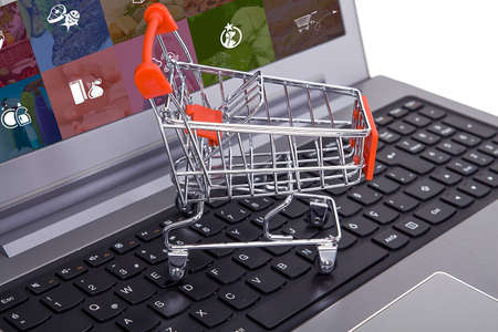 Computer and small toy shopping cart on table. Internet shopping concept.