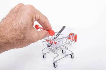 Small toy shopping cart in the hands of the man doing internet shopping. Internet shopping concept. Stok Fotoğraf