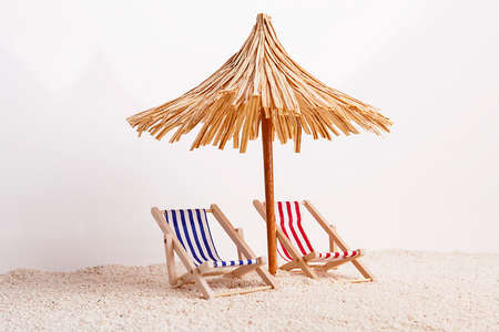 Toy chaise longue and sun umbrella on sandy beach, on sunny day at the white background. Relaxation concept.