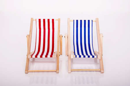 Toy chaise longue on sunny a day at the white background. Relaxation concept.