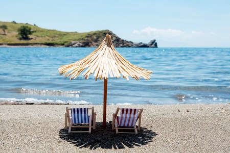 Toy chaise longue and sun umbrella on sandy beach on sunny day at the blue sea background. Relaxation concept. 写真素材
