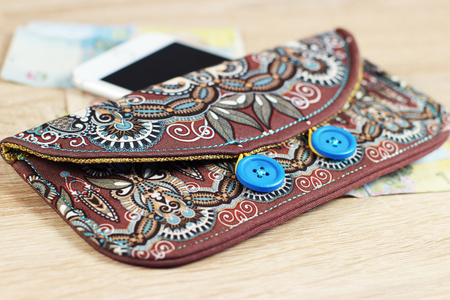 capacious: female purse money artists design with two wooden buttons on wood background, handmade floral paisley pattern