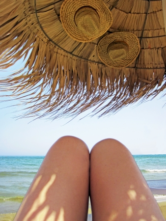 Legs of the woman sunbathing under the sunshade with 2 hats                     photo