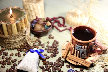 etnic: Still life with ceramic cup of coffee, coffee grains, bamboo candle and etnic beads on background