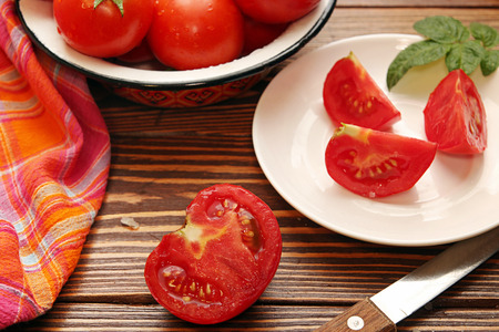 cutted: Fresh ripe tomatoes in bowl, half of cutted tomato and chopped tomatoes on white souser