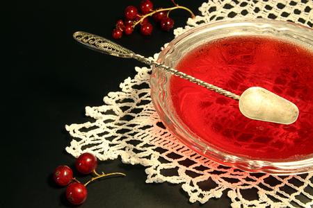gelatina: mermelada de grosella roja en un tazón de vidrio contra el fondo negro. servilleta de encaje y hermoso dessertspoon
