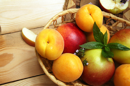 wattled: Apricots and apples in wattled basket on a wooden table.