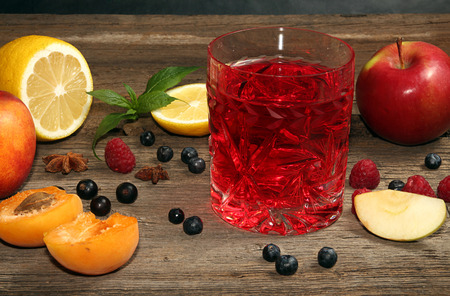 sweet vermouth: Glass of compot of apples, apricots, raspberry, bilberry, blackcurrant on wooden old table