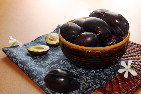 homegrown: Organic homegrown plums in ceramic bowl over on table Stock Photo