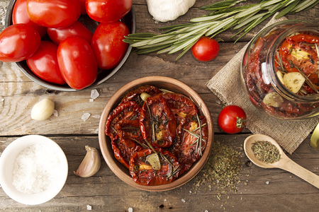 spice: Preparation dried tomatoes. Raw and dried tomatoes arranged over on old wooden table  with spice and herbs. Rustic stile. Organic healthy food concept. Top view