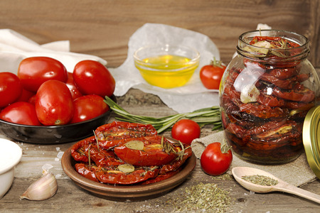 Preparation dried tomatoes. Raw and dried tomatoes arranged over on old wooden table  with spice and herbs. Rustic stile. Organic healthy food concept Stock Photo