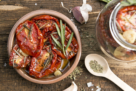 legumbres secas: Preparation dried tomatoes. Raw and dried tomatoes arranged over on old wooden table  with spice and herbs. Baking tray with raw tomato. Rustic stile. Organic healthy food concept