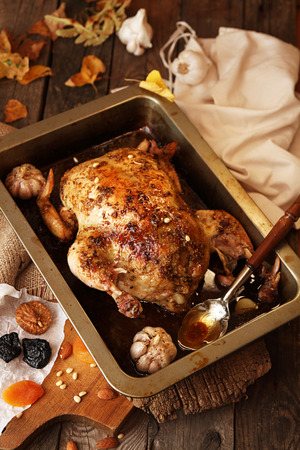 roasting pan: Roasted small turkey for celebration Thanksgiving day in roasting pan on old rustic wooden table. Stuffed with couscous with a fig, prunes, dried apricots, almonds and pine nuts Stock Photo