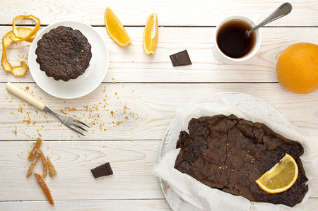 Still life with chocolate cupcake with dried orange peels, chocolate cake in parchment paper, cup of tea, orange and candied orange peels used in recipe arranged on white wooden table