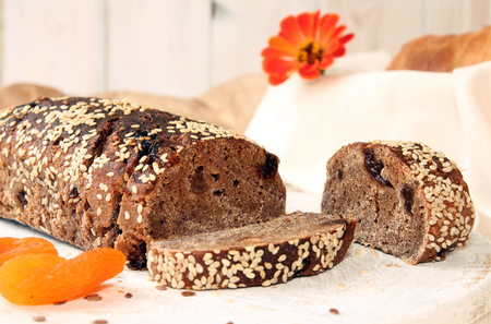 Loaf of rye unleavened  bread without yeast with dried apricots and raisin sprinkled seeds of flax and sesame