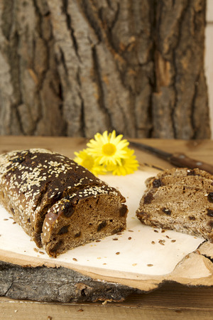 Loaf and slices of rye unleavened  bread without yeast with raisin sprinkled seeds of flax and sesame