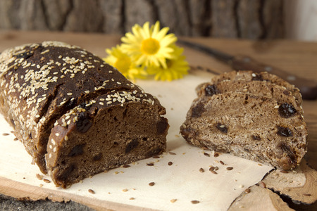 Loaf and slices of rye unleavened  bread without yeast with dried apricots and raisin sprinkled seeds of flax and sesame