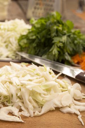白いキャベツ、すりおろしたニンジン、フェンネル、パセリ、サラダやザワークラウトの古い木製のテーブルの上に配置を準備するための成分をス