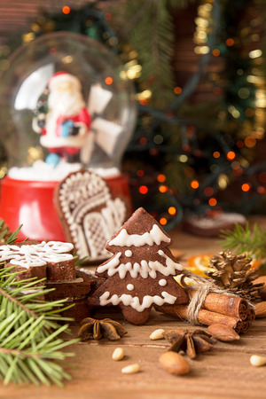 Christmas gingerbread cookies against background glass sphere with snow and Santa Klaus, branch of fir tree and sparks of Christmas garland Stock Photo