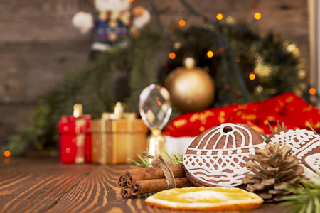 Cristmas gingerbread cookies and bell against background branch of Christmas tree, gifts and snowman on old wooden background Stock Photo