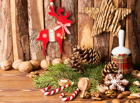 newyear: Christmas decorations. Gingerbread cookies, walnuts, Christmas bell, fir tree  branch, cone and Christmas star and deer against background pine logs Stock Photo