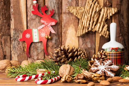 Christmas decorations. Gingerbread cookies, walnuts, Christmas bell, fir tree  branch, cone and Christmas star and deer against background pine logs Stock Photo