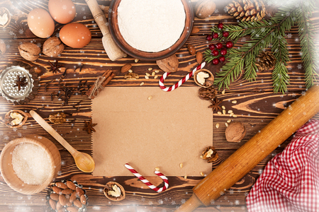 sweeties: Preparation Christmas New Year sweeties. Ingredients and holiday decorations over on wooden table. Decorated with snow and snowflakes. Image for greeting card. Top view. Copy space.