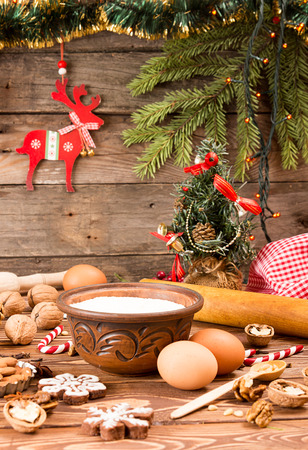 sweeties: Preparation Christmas New Year sweeties. Ingredients and holiday decorations over on wooden table against old wooden background with fir tree branch, small Christmas tree and red deer. Image for greeting card.
