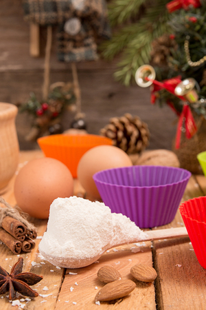 sweeties: Spoon with flour on foreground. Preparation Christmas New Year sweeties. Ingredients and holiday decorations over on wooden table against old wooden background with fir tree branch, small Christmas tree. Closeup.