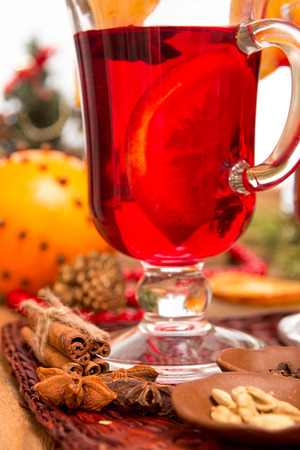 Glass of mulled wine over on wooden table. Christmas concept.