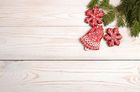 クリスマス正月休日背景。赤のジンジャーブレッドのクッキーと白いテーブルにモミ枝。平面図です。コピー スペース