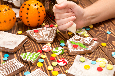 cornet: Creation Christmas gingerbread house. Hands with icing cornet. Assembly gingerbread house over on  wooden table. Multi-colored parts of gingerbread house Stock Photo