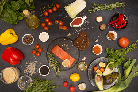 Healthy food table cooking ingredients. Overhead of salmon fish, fresh vegies and seasoning. Organic vegetable and herbs: paprika,  avocado, cherry tomato, Beijing cabbage, chili, lemon,  spinach, arugula, rosemary on black background. Top view. View from