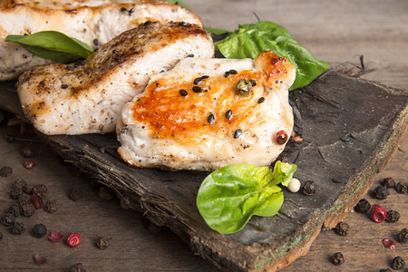 Grilled turkey fillet with bright appetizing roasted crust garnish spinach and black sesame seeds on tree bark dish on old wooden table. Rustic style