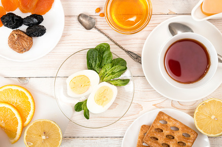 Healthy breakfast. Boiled eggs with spinach, orange juice, cup of tea, honey, cookies and dried fruits on white table. Healthy organic natural food concept. Top view. View from above Stock Photo