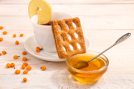 argousier: Morning breakfast. Cup of tea with lemon, cookie with delicious sea buckthorn jam. Fresh sea-buckthorn on white wooden background. Composition in white and orange colors