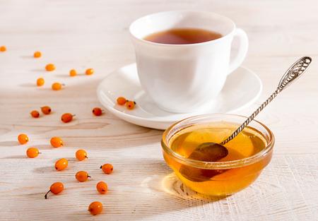argousier: Morning breakfast. Cup of tea with delicious sea buckthorn jam. Fresh sea-buckthorn on white background.