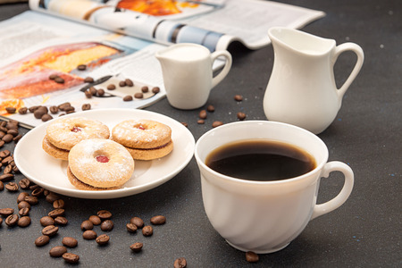 Cup of coffee, saucer with cookies, milk jug, roasted coffee beans and culinary magazin over on dark tabletop.  Stock Photo