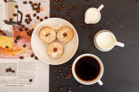 Coffee break. Cup of coffee, saucer with cookies, milk jug, roasted coffee beans and culinary magazin over on dark tabletop. Top view. View from above