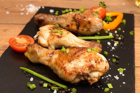 Jambes de poulet frits garnir de tomates cerises et d'oignons de printemps sur une ardoise noire